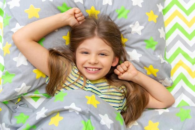 어린 소녀는 아침에 침대에 누워서 미소를 짓습니다.