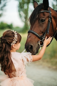 小さな女の子が頭に彼女のお気に入りの馬を撫でる