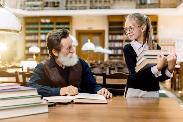 Маленькая ученица ученица держит много книг в руках и смотрит на своего старшего бородатого учителя, сидящего за столом и читающего книги в старинной библиотеке