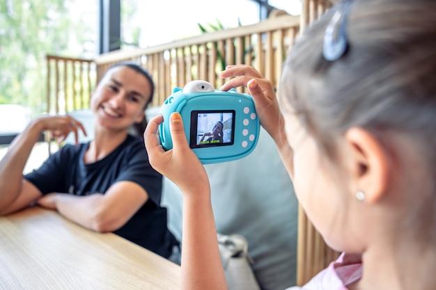 어린 소녀는 즉석 사진 인화를 위해 카메라로 어머니의 사진을 찍습니다.