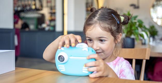 어린 소녀는 즉석 사진 인쇄를 위해 카메라로 사진을 찍습니다.