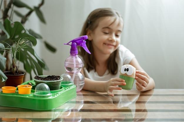 小さな女の子が草が生えるおもちゃの世話をします。