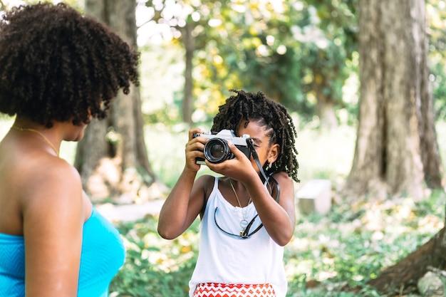 여자의 오래 된 카메라와 함께 사진을 찍는 어린 소녀. 어린 시절 개념