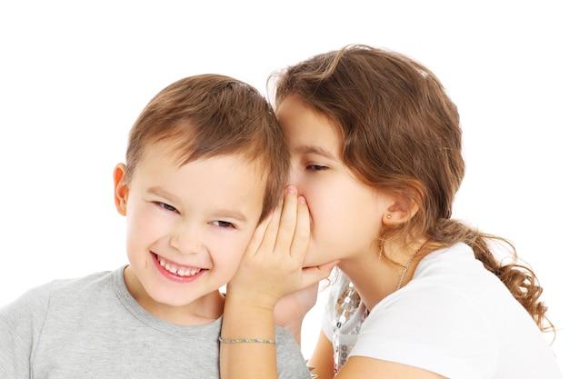 Маленькая девочка рассказывает секрет своему брату на белом фоне