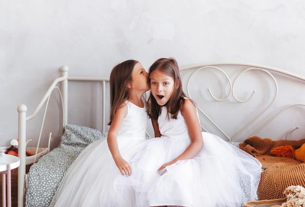 小さな女の子が友達の耳に秘密を告げる。かわいい子供たちは明るい部屋で遊ぶ