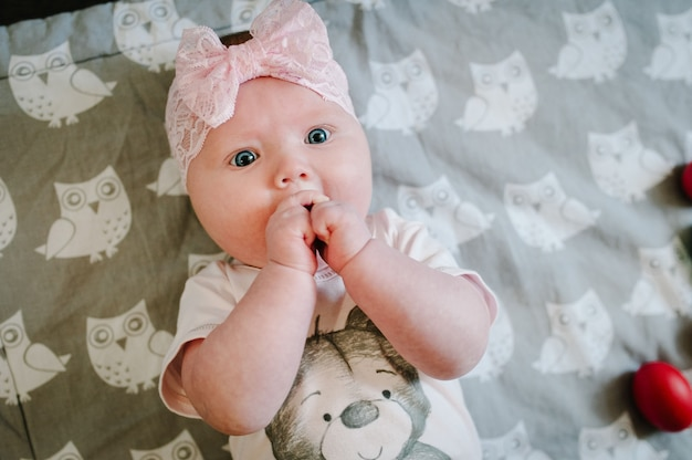 生まれたばかりの小さな女の子、赤ちゃんは、ベッドの上の灰色の柔らかい毛布の表面に横たわり、手と笑顔で遊んでいます。写真撮影は4-5ヶ月。フラットレイ。上面図。