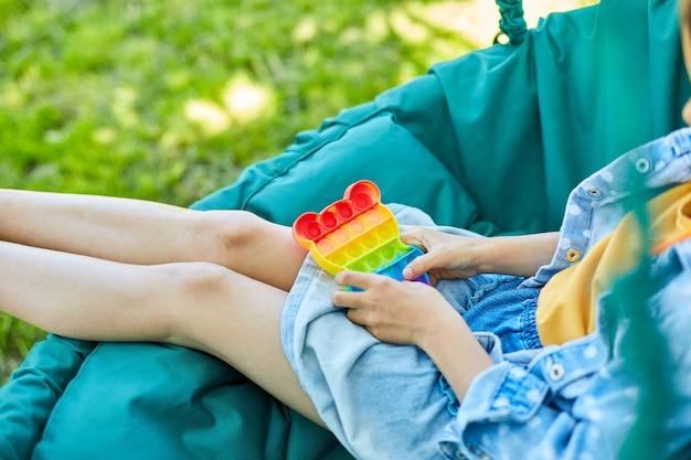 Маленькая девочка на подвесном стуле на открытом воздухе играет в поп, детские руки играют с красочными хлопками, игрушка-непоседа на заднем дворе дома в солнечный летний день, летние каникулы.