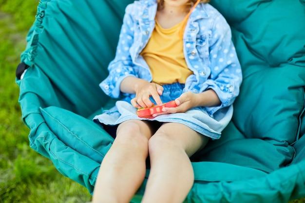 Маленькая девочка на подвесном стуле на открытом воздухе играет в поп, детские руки играют с красочной поп-музыкой