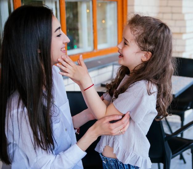 어린 소녀는 부드럽게 어머니의 얼굴을 만집니다. 가족 레저 및 레크리에이션. 산모의 보살핌과 사랑. 어머니의 날과 3월 8일.