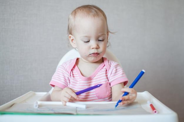 어린 소녀가 펠트펜으로 그림을 그리려고합니다.
