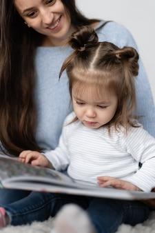 Маленькая девочка двух лет сидит с мамой на коленях. оставайся дома. мама с дочерью читает большую бумажную книгу. интересные детские сказки