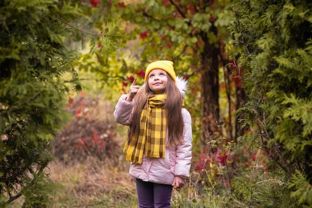 小さな女の子が秋の公園を歩きます。