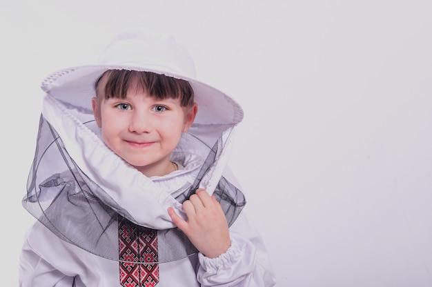 小さな女の子は、スタジオの白い背景で特大の蜂のスーツを着ています。
