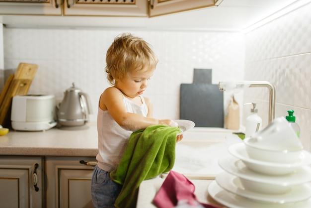 小さな女の子が台所の皿を拭きます。家で家事をしている赤ちゃん。