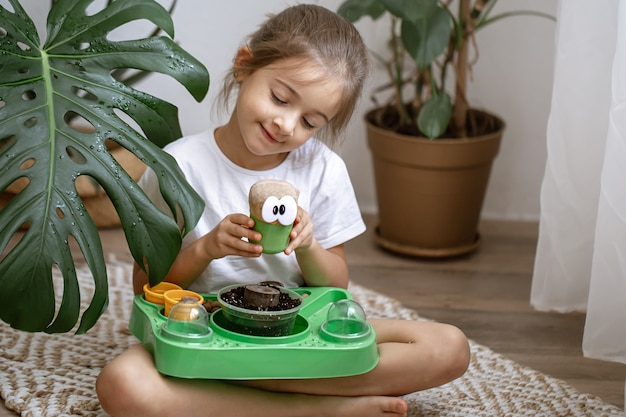 Маленькая девочка с детским набором для самостоятельного выращивания растения.