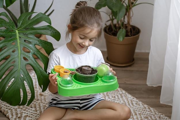 식물을 스스로 키울 수 있는 아기 키트를 가진 어린 소녀입니다.