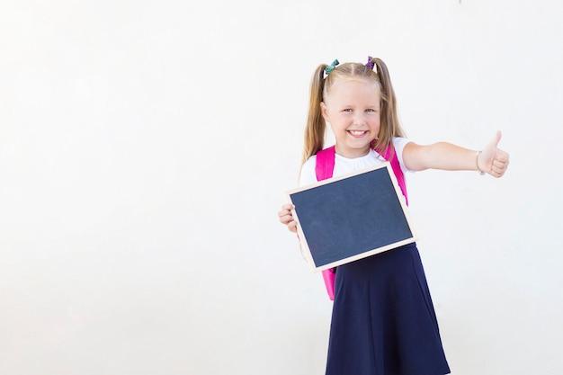 Маленькая девочка с рюкзаком показывает палец вверх. школа