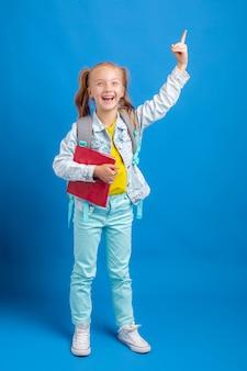 Маленькая девочка с рюкзаком держит книгу на синем фоне