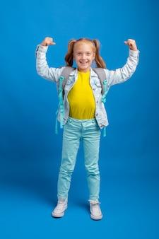 Маленькая девочка с рюкзаком показывает сильную на синем фоне