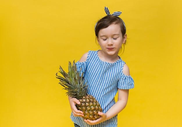 눈가리개와 줄무늬 티셔츠를 입은 어린 소녀가 눈을 감고 서서 텍스트를위한 공간이있는 노란색 벽에 파인애플 과일을 들고 있습니다.