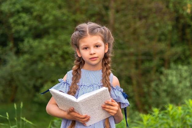 緑の公園で本を持った少女。