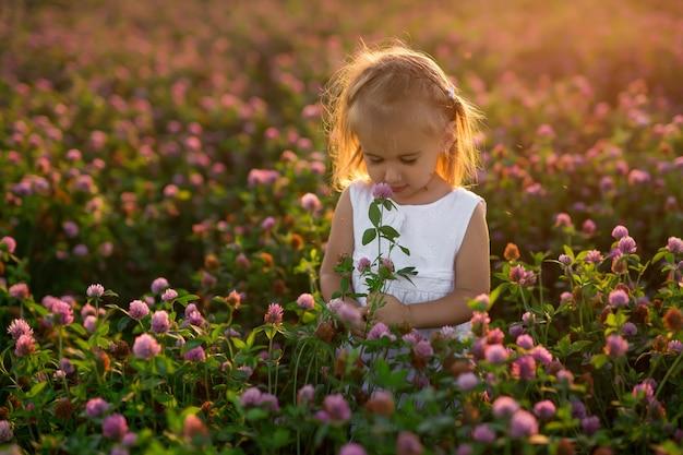 クローバー畑に花の花束を持った少女が蚊に刺される