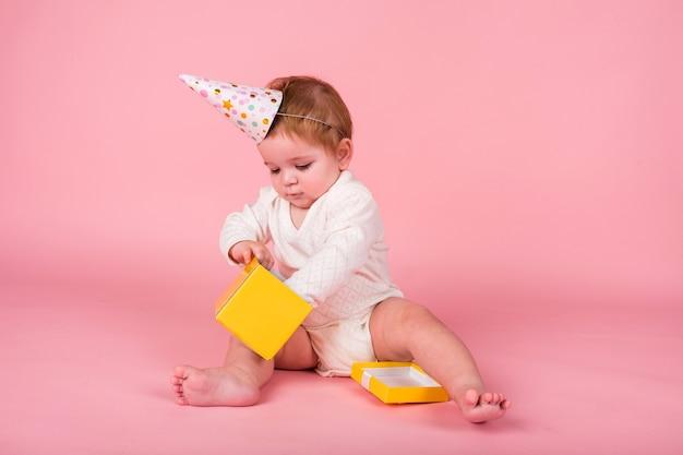 休日の帽子をかぶった少女は、テキスト用のスペースがあるピンクの壁に黄色のボックスで開きます