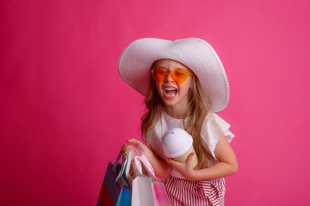 쇼핑백을 많이 들고 선글라스와 모자를 쓰고 웃는 어린 소녀