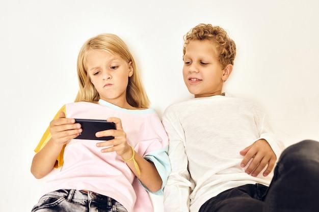 手に携帯電話を持った少女が男の子の隣で遊ぶ