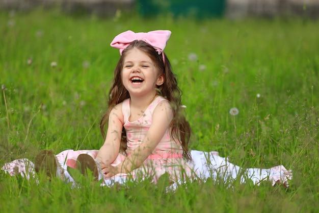 ピンクの弓を持った少女が草の上に座って笑っています。高品質の写真