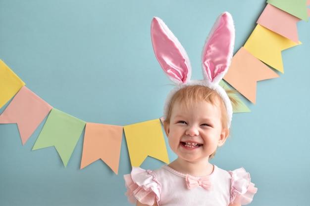 Маленькая девочка с улыбкой в кроличьих ушах. пасха. счастливый ребенок.