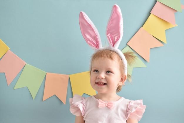 旗と青い背景に彼女のウサギの耳に笑顔の少女。