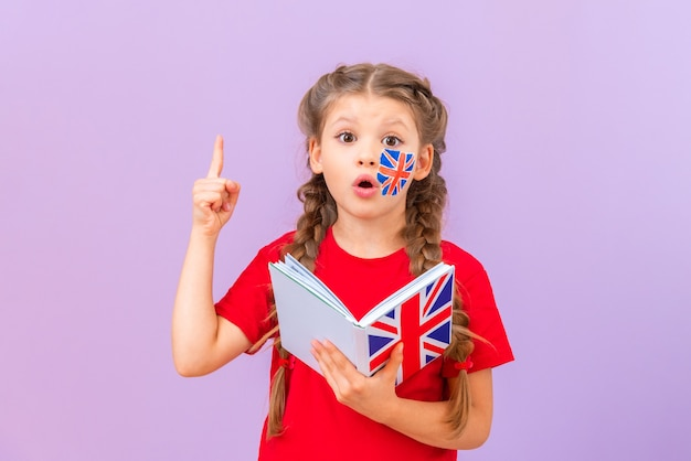 Маленькая девочка с английской книгой удивленно показывает вверх.
