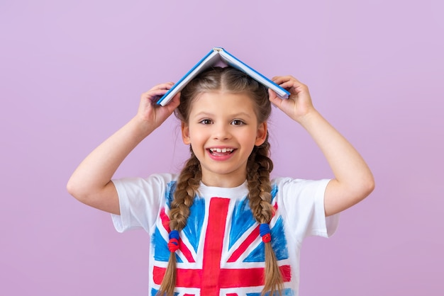 Tシャツに英語の旗を掲げた少女が頭に本を持っています。