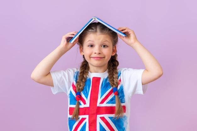 Маленькая девочка с английским флагом на футболке держит книгу над головой.