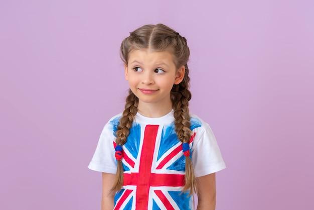 티셔츠에 영국 국기가 달린 어린 소녀가 시선을 돌립니다.