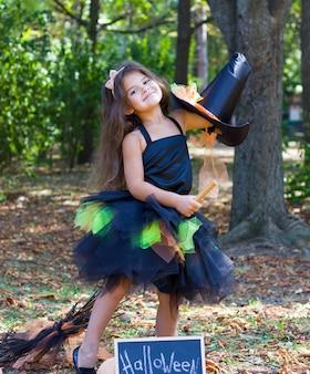 手にほうきを持った魔女の衣装を着た黒い髪の少女。