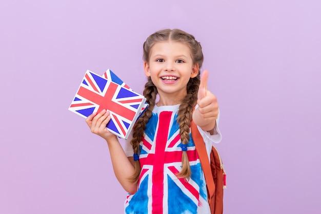 영어 책을 든 어린 소녀가 엄지손가락을 치켜세웁니다.