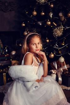 Маленькая девочка с каштановыми волосами на темном фоне в милом платье. золотой и черный. елка и новогодние украшения