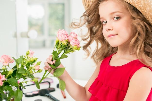 化粧品を持つ少女。彼女は母親の寝室で鏡の近くに座っています。