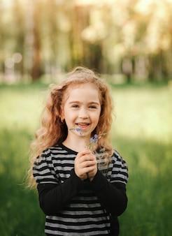 여름에 공원에서 곱슬머리를 한 어린 소녀가 카메라를 쳐다본다