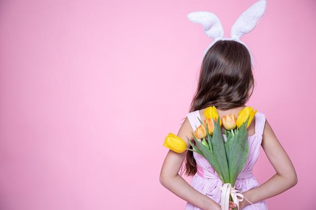 Маленькая девочка с ушками пасхального кролика держит в руках за спиной букет тюльпанов на розовом студийном фоне