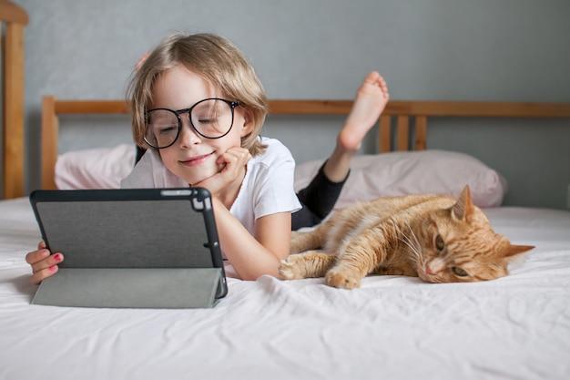 안경을 쓴 어린 소녀가 온라인으로 숙제를 하고 있다 뚱뚱한 생강 고양이가 근처에 누워 있다