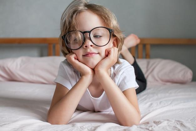 안경을 쓴 어린 소녀가 새 학기 시작의 개념으로 침대에 누워 있다