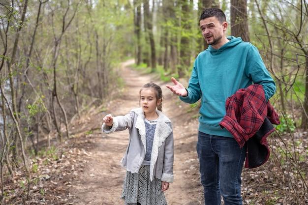 Маленькая девочка с папой гуляют по весеннему лесу и что-то обсуждают.