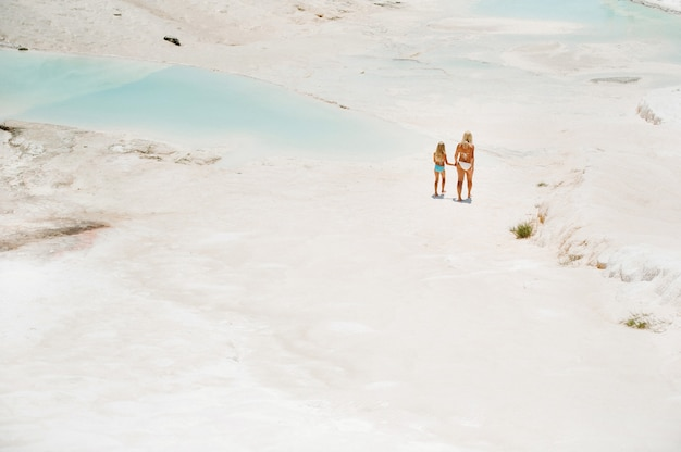 白い山で水着とサングラスをかけた母親と一緒の少女、別の惑星、パムッカレ、トルコの晴れた夏の日の家族