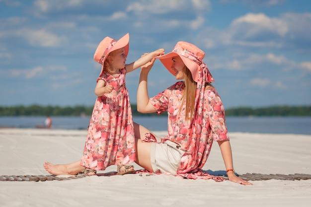 美しいサンドレスを合わせた母親と一緒の少女がビーチの砂浜で遊んでいます。スタイリッシュなファミリールック。