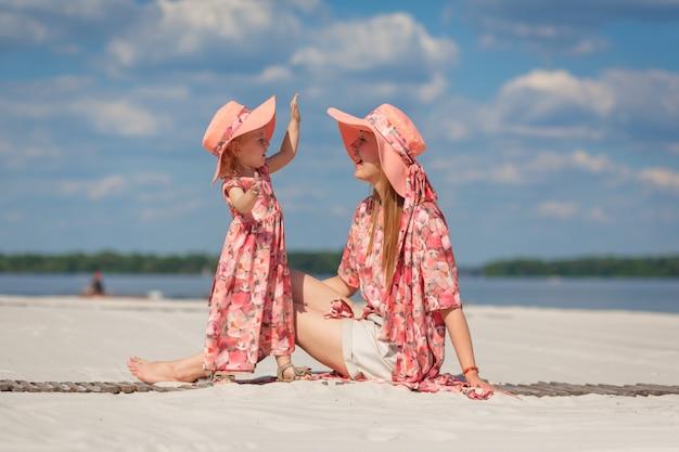 美しいサンドレスを合わせて母親と一緒に小さな女の子がビーチの砂で遊ぶ