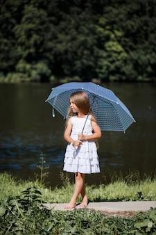 白いドレスを着た長い髪の少女が川のほとりに立っています。夏の晴れた日に湖のほとりを歩く