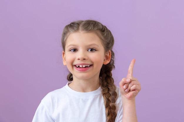 땋은 머리와 흰색 티셔츠를 입은 어린 소녀가 가리 킵니다.